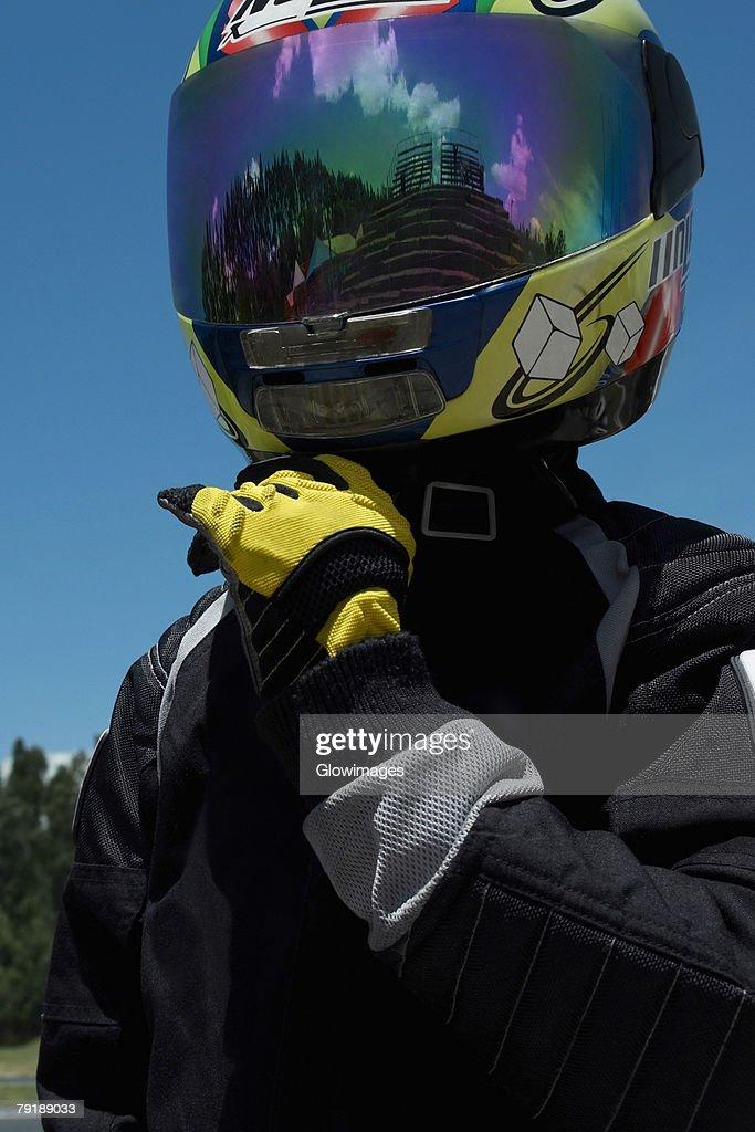 Close-up of a person adjusting his crash helmet : Stock Photo