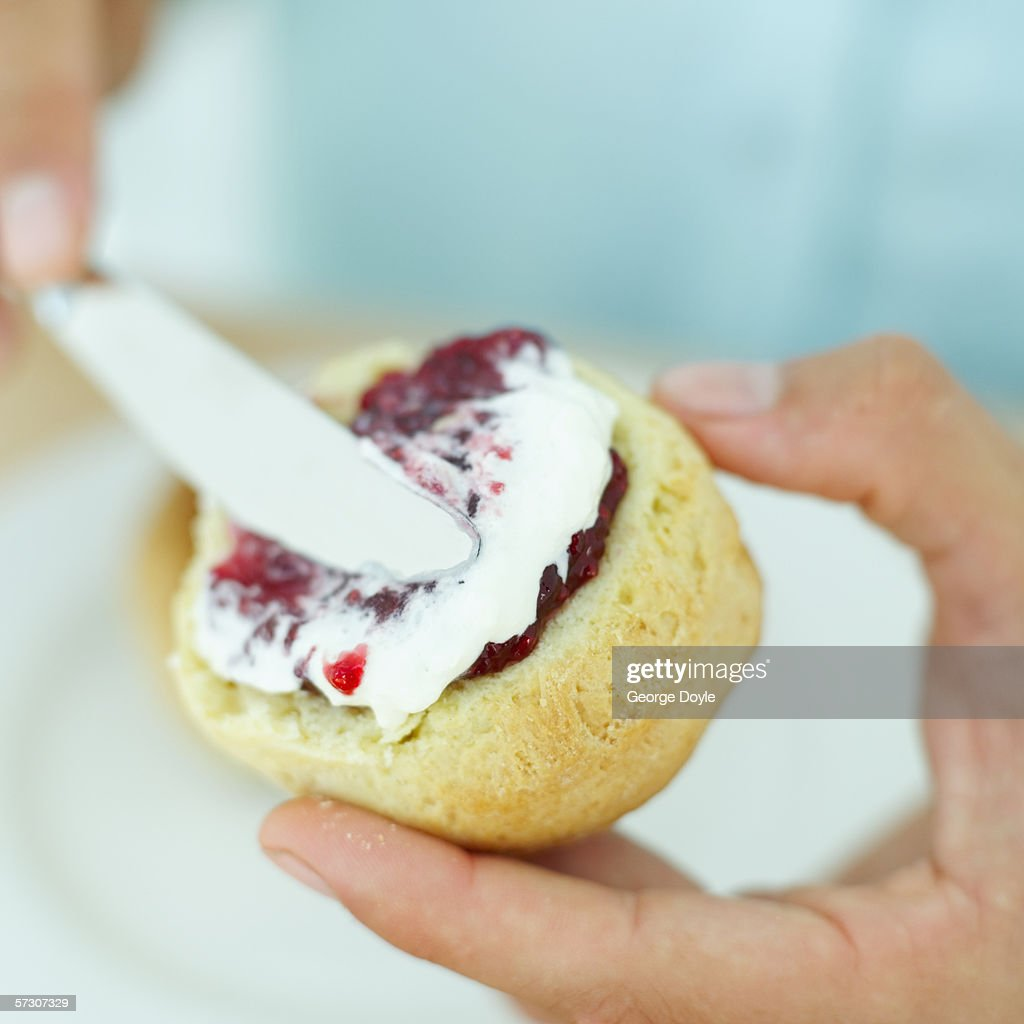 Close-up of a person applying jam on a pastry : Stock Photo