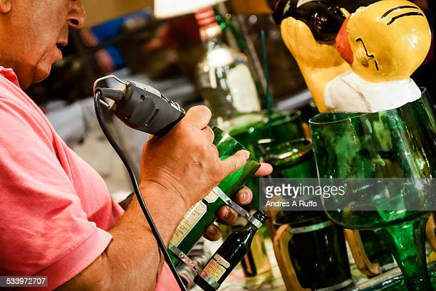 Closeup of a person craftsman man using with his hand a small lathe on a glass bottle on the promenade of artisans in the center of the city of...