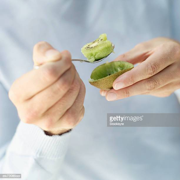close-up of a person eating a kiwi with a spoon - kiwi fruit stock pictures, royalty-free photos & images