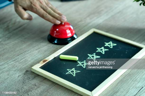 Close-up Of A Person Hand Ringing Service Bell Near Five Star on the blackboard