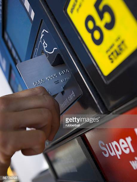 Close-up of a person paying for gas with a credit card
