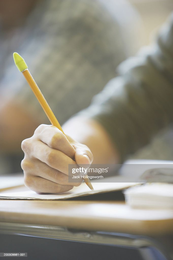 Close-up of a person writing in a book : Stock Photo