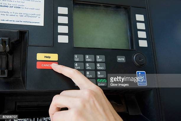 Close-up of a person's finger using a gas station machine