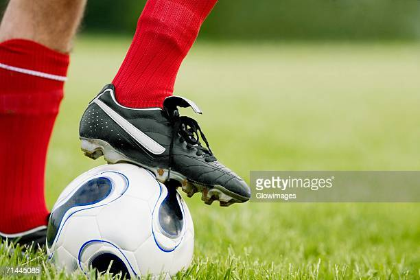 Close-up of a person's foot resting on a soccer ball