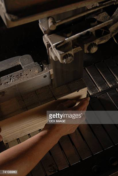 Close-up of a person's hand cutting wood in a workshop
