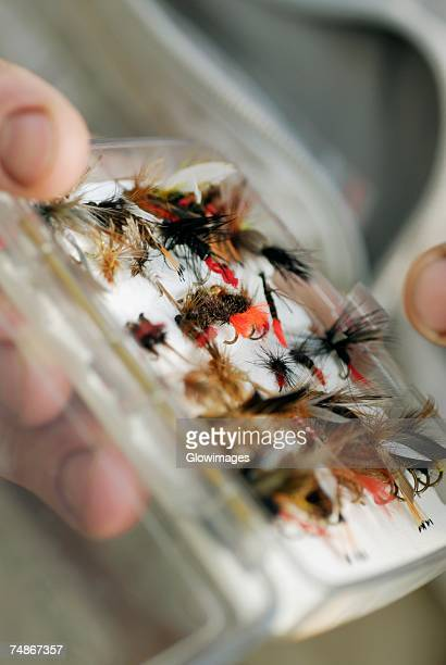 Close-up of a person's hand holding a box of flies and lures
