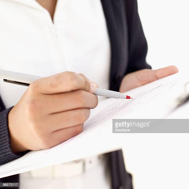 close-up of a person's hand holding a pen and a notepad - enfermera fotografías e imágenes de stock