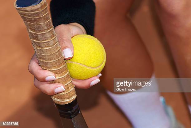Close-up of a person's hand holding a tennis racket with a tennis ball