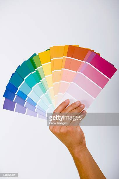 close-up of a person's hand holding color swatches - color swatch stock pictures, royalty-free photos & images