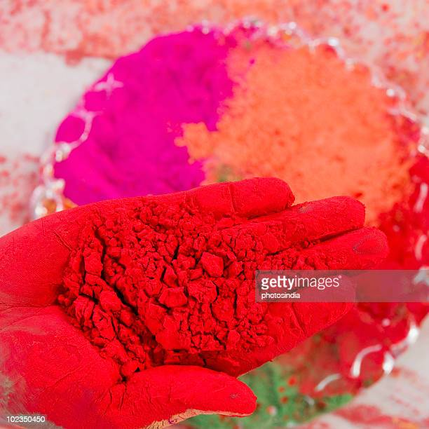 Close-up of a person's hand holding Holi colors