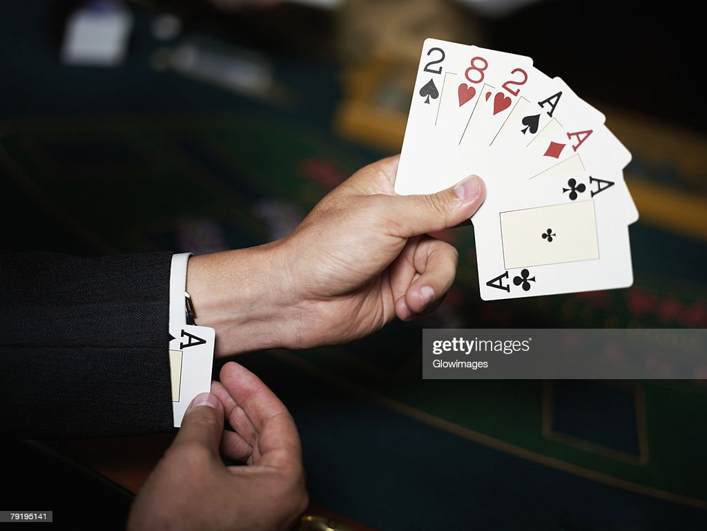 Close-up of a person's hand holding playing cards and hiding an ace in his cuff : Stock Photo