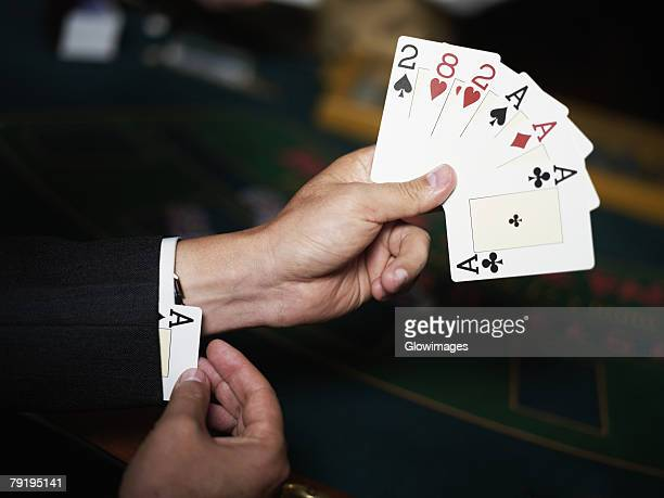 Close-up of a person's hand holding playing cards and hiding an ace in his cuff