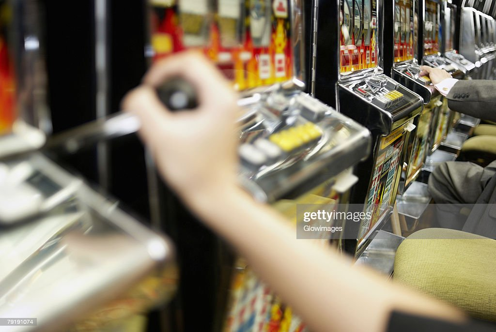 Close-up of a person's hand holding the lever of a slot machine : Foto de stock