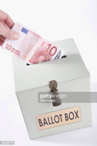 Close-up of a person's hand inserting ten euro banknote into a ballot box