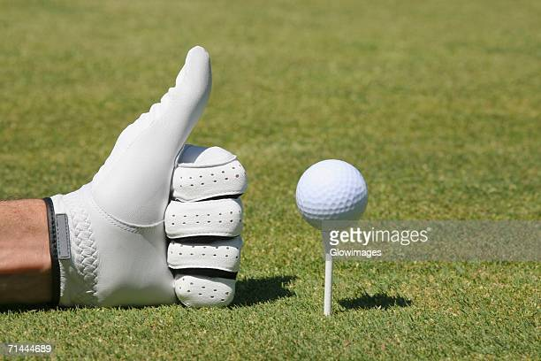 Close-up of a person's hand making a thumbs up sign next to a golf ball on a tee