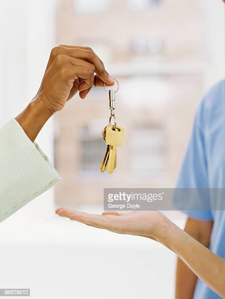 close-up of a person's hand offering a key ring to another person's hand