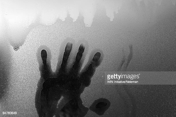 Close-up of a person's hand on a window glass
