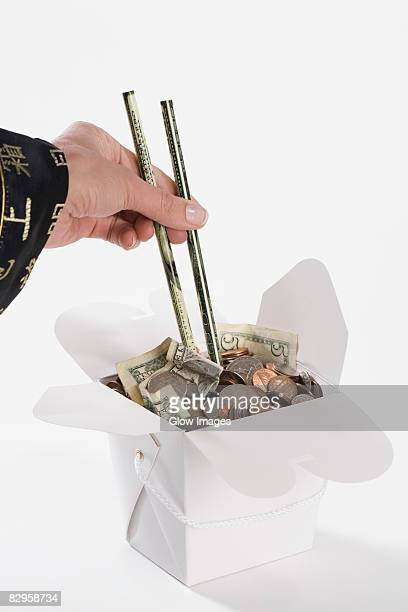 Close-up of a person's hand picking coins with chopsticks