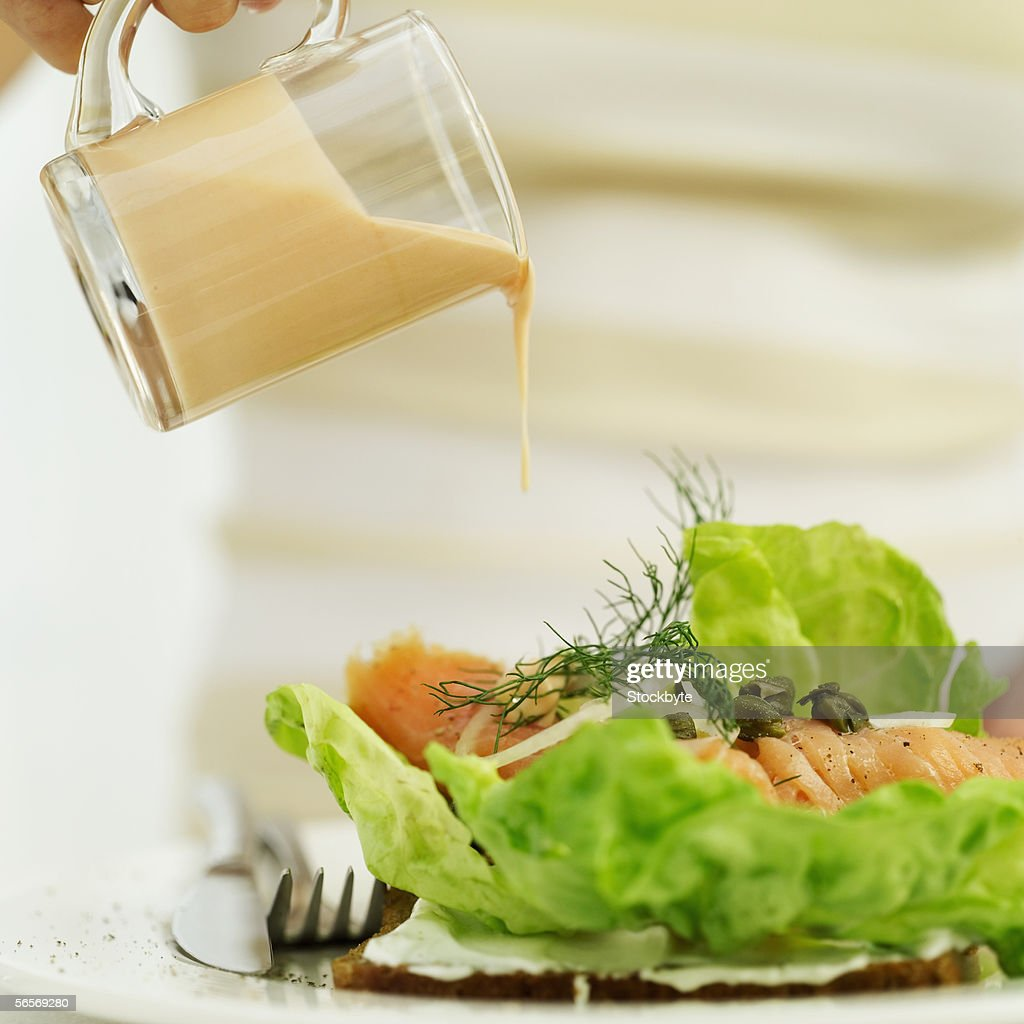 close-up of a person's hand pouring a jug of salad dressing over a sushi salad : Stock Photo