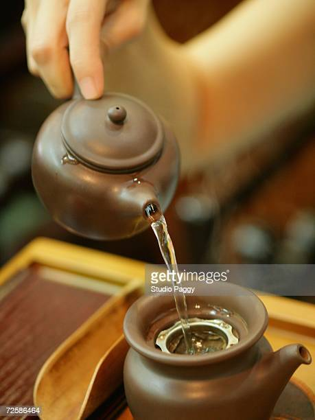 Close-up of a person's hand preparing tea