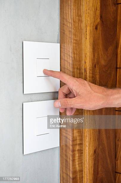 Close-up of a person's hand pressing a light switch