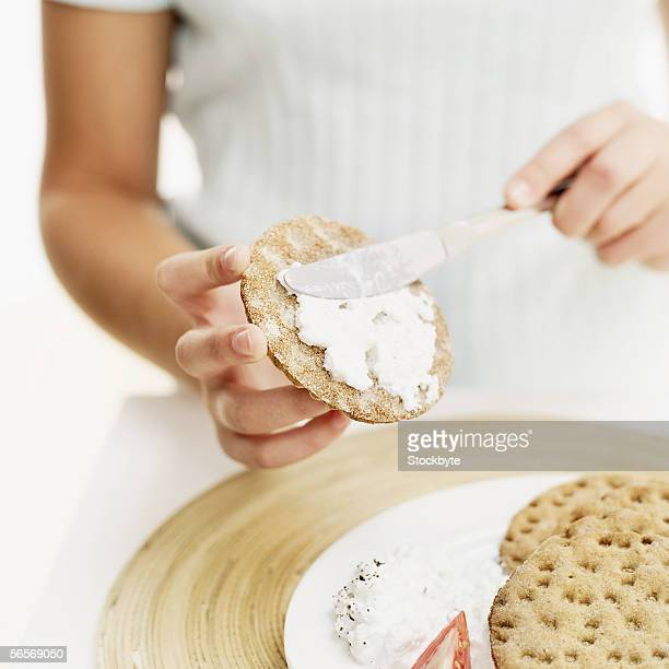 close-up of a person's hand spreading dip on a cracker