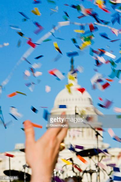Close-up of a person's hand throwing confetti at a gay parade