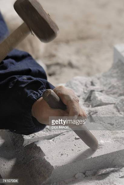 Close-up of a person's hand using a chisel and a hammer on a stone