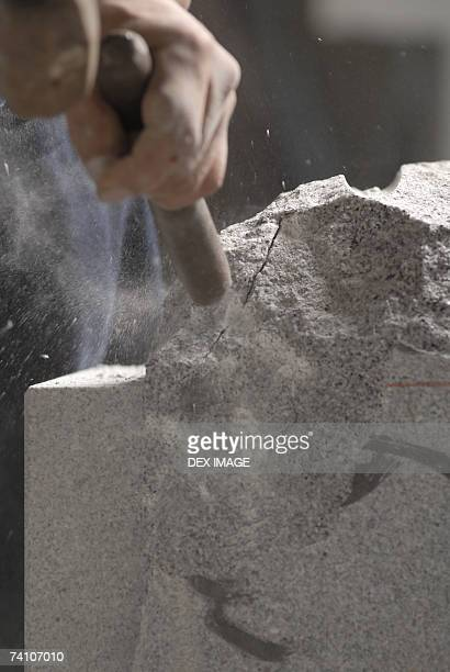 Close-up of a person's hand using a chisel and a hammer on stone