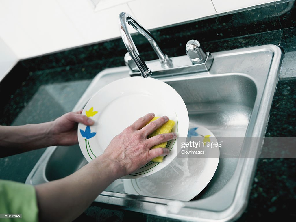 Close-up of a person's hand washing plate in the kitchen : Foto de stock