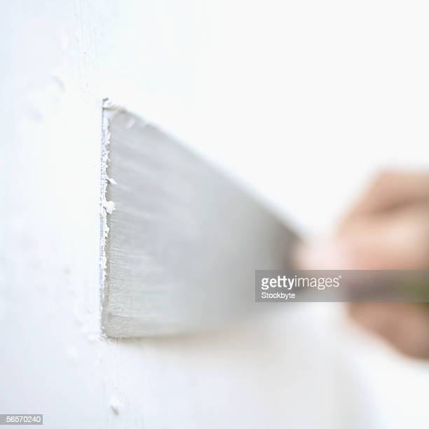 close-up of a person's hands applying filler to a wall with a putty knife