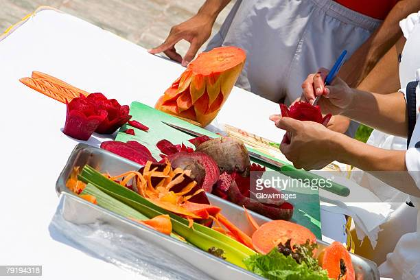Close-up of a person's hands carving fruits and vegetables, Cancun, Mexico