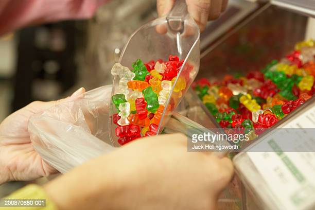Close-up of a person's hands putting Gummy bears into a packet