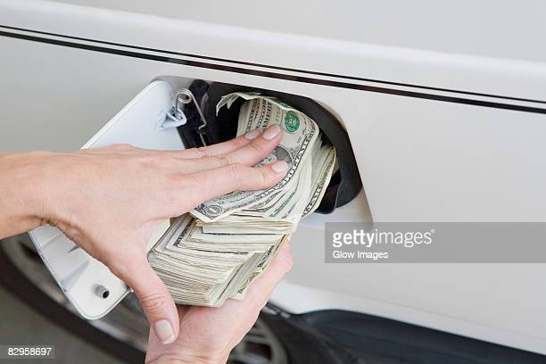Close-up of a person's hands putting US paper currency in a gas tank of a car