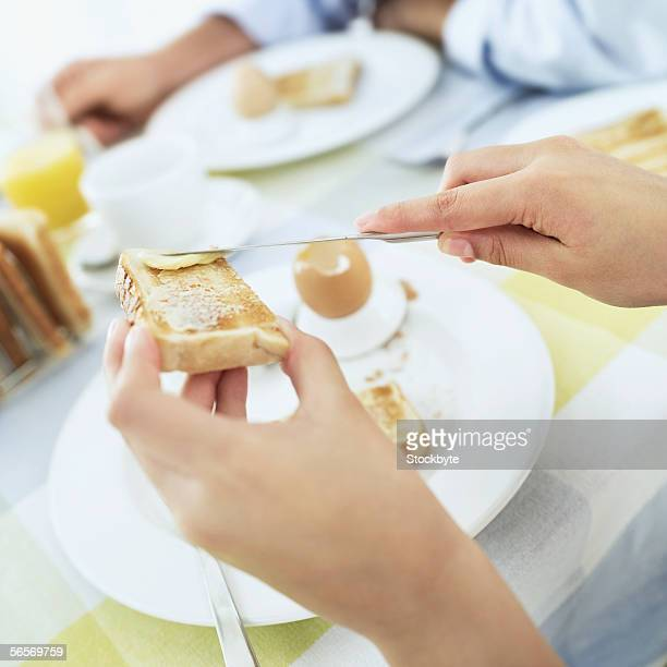 close-up of a person's hands spreading butter on a slice of toast