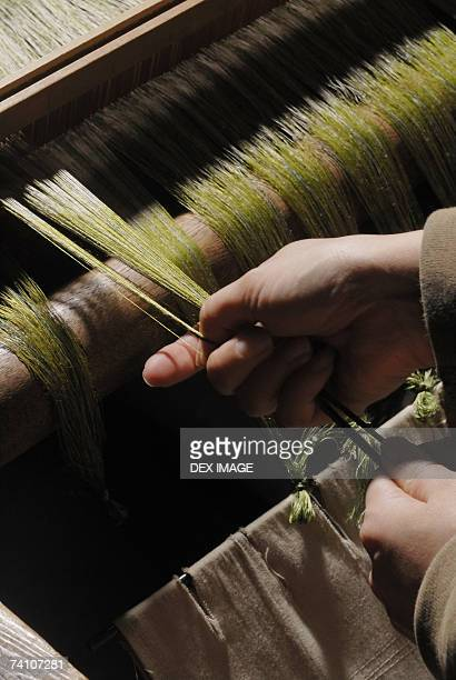 Close-up of a person's hands working on a loom