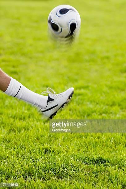 Close-up of a person's leg kicking a soccer ball