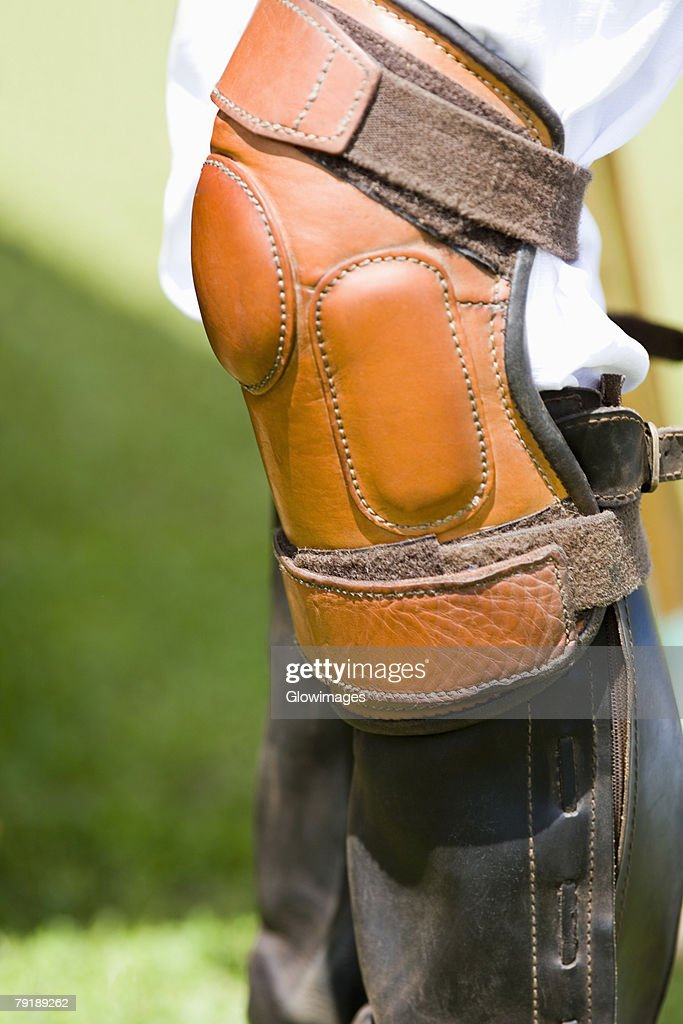 Close-up of a person's legs wearing riding boots and a kneepad : Foto de stock