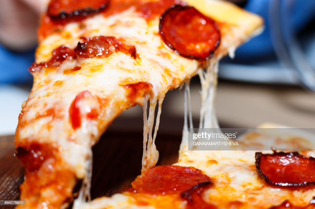 Closeup of a piece of pepperoni pizza. Italian pizza. : Stock Photo