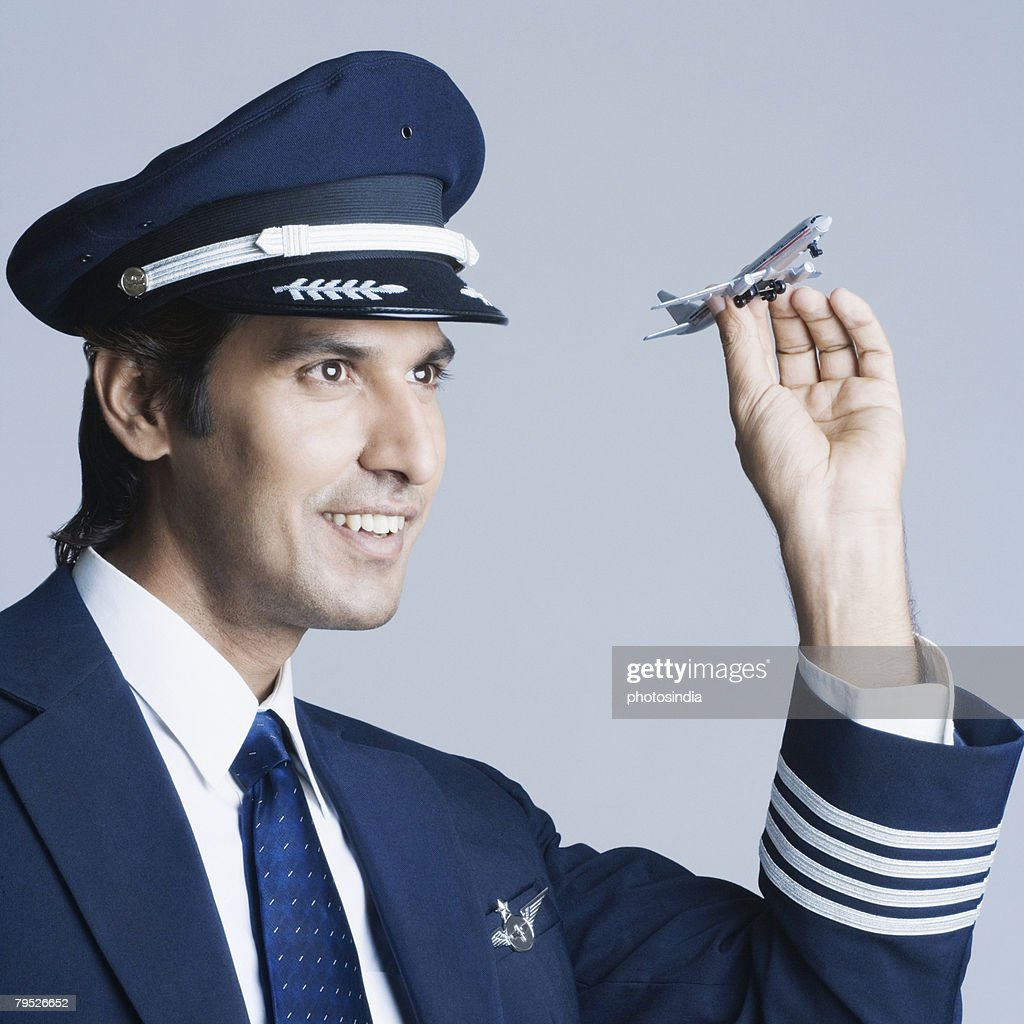 Close-up of a pilot holding a toy airplane and smiling : Stock Photo