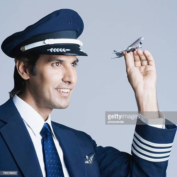 Close-up of a pilot holding a toy airplane and smiling