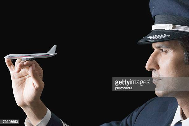Close-up of a pilot with a toy airplane on his fingers