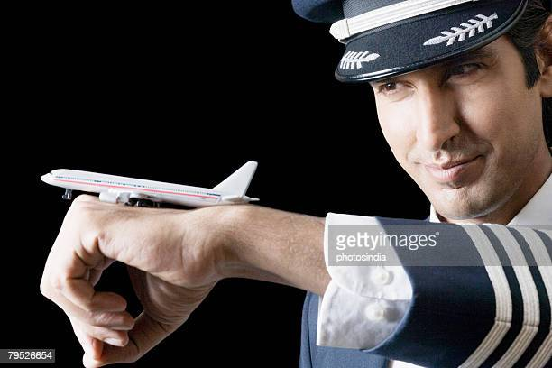 close-up of a pilot with a toy airplane on his hand - uniform cap stock pictures, royalty-free photos & images