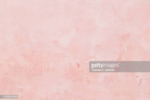 closeup of a pink concrete wall - muur stockfoto's en -beelden