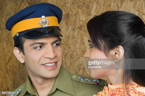 Close-up of a police man with his wife looking at each other and smiling