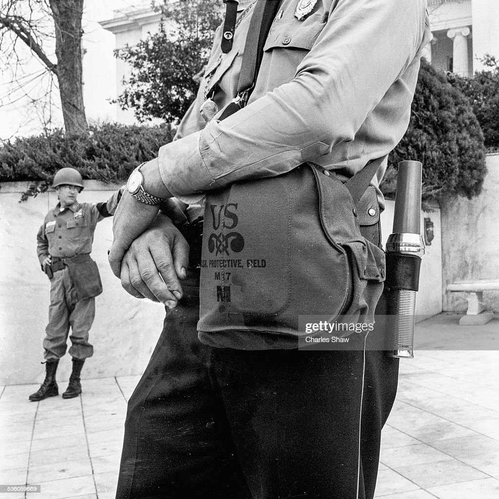 Close-up of a police officer in front of the Alabama State Capitol building at the end of the Selma to Montgomery March, Montgomery, Alabama, March 25, 1965. A US Army MP stands behind him.