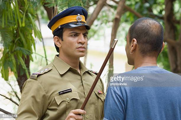 Close-up of a policeman showing a nightstick to a young man