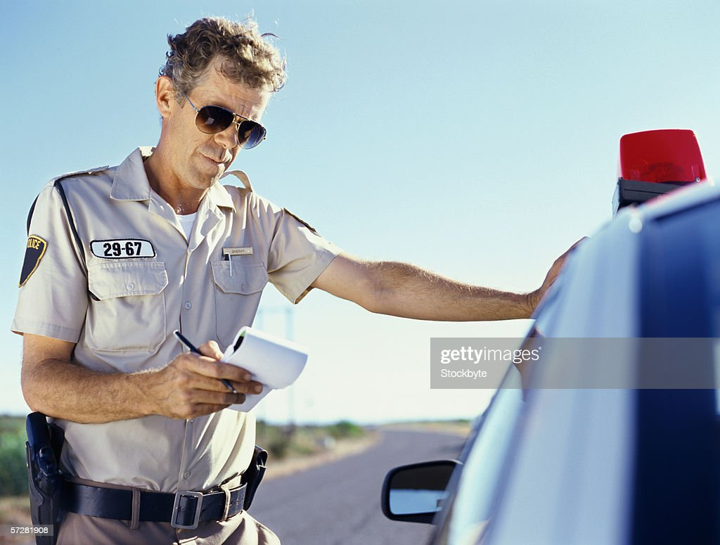 Close-up of a policeman standing near a car and looking at notebook : Stock Photo