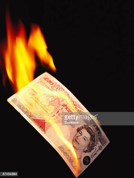 close-up of a pound note on fire